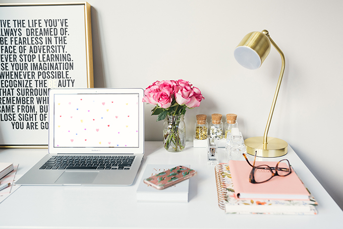 White desk with pink flowers, gold lamp, notebooks, glasses, and a Mac laptop on a desk displaying watercolor hearts valentine's day wallpaper