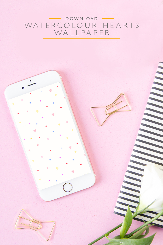 iPhone displaying a watercolor hearts wallpaper on pink background with gold bowtie paper clips, a striped notebook and a flower