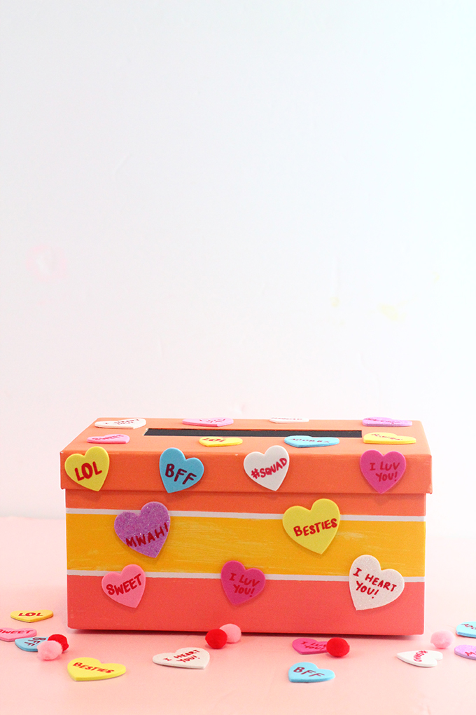 A colorful valentine's day mailbox covered in conversation heart stickers with origami hearts beside