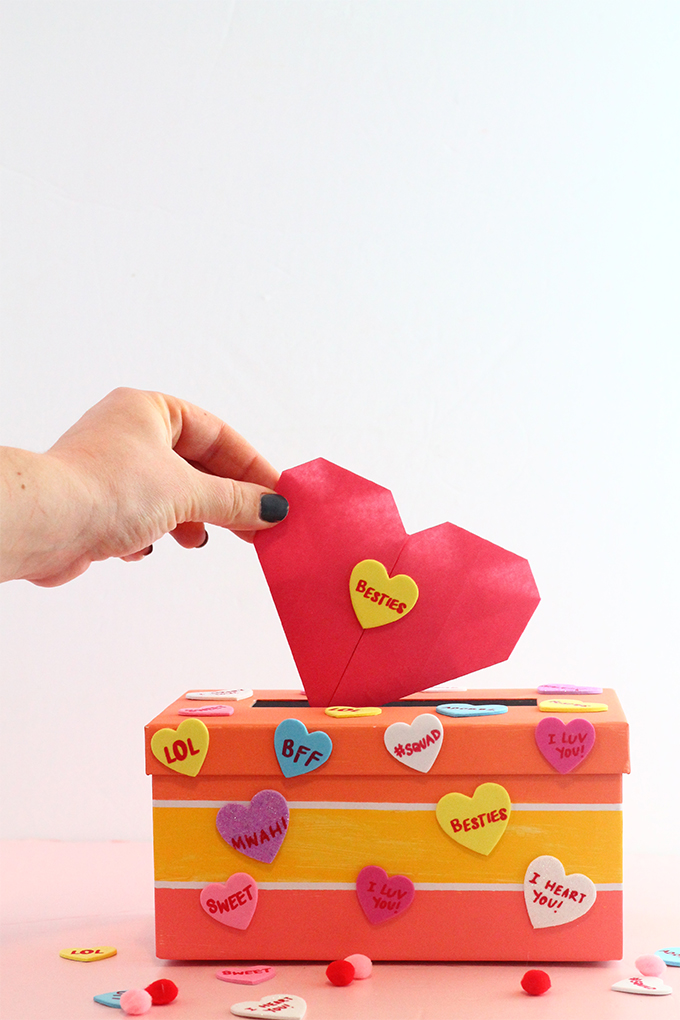 Hand putting a pink origami heart into a colorful valentine's day mailbox covered in conversation heart stickers