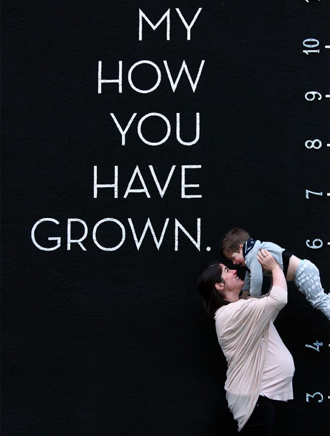 Black background with mother holding up toddler boy and the words written on the wall, my how you have grown